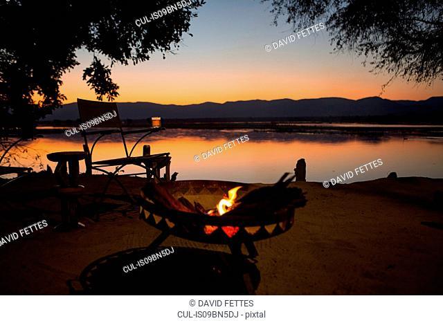 Fire by Zambezi River at sunset, Mana Pools, Zimbabwe