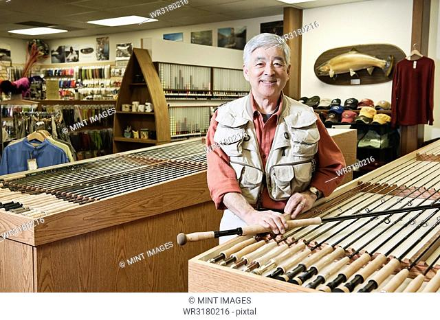 Portrait of an Asian American senior male owner of a retail fly- fishing shop, who is wearing a fly fishing vest