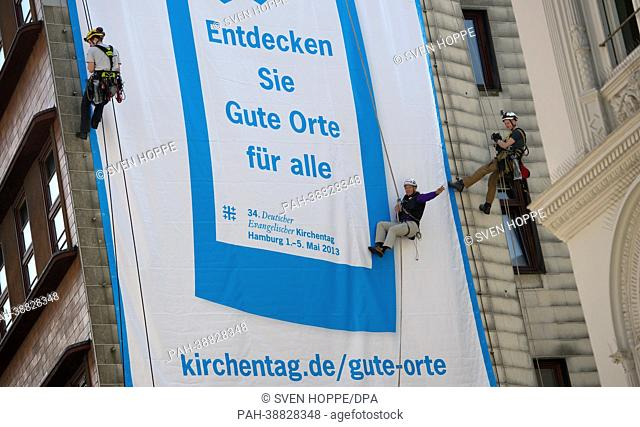 Blind extreme athlete Andy Holzer (C) rappels from a highrise under the motto 'Church Congress Handicapped Accessible' in Hamburg, Germany, 16 April 2013