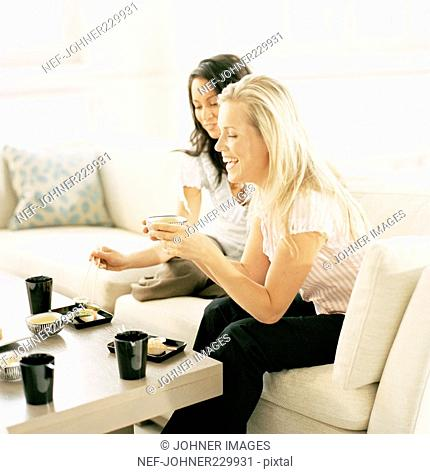Two women eating sushi in a sofa