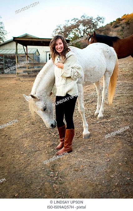Portrait of young woman petting white horse