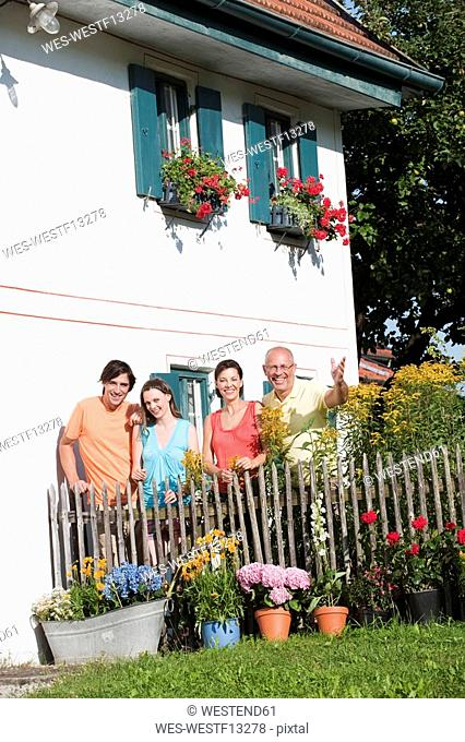 Germany, Bavaria, Four persons standing at garden fence, portrait