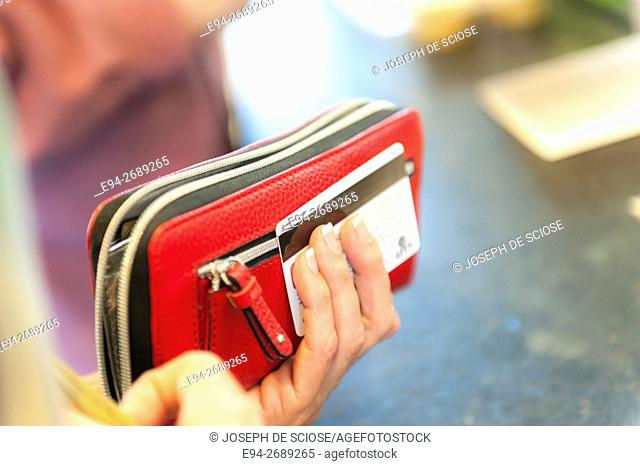 A woman's hand holding a wallet and a credit card