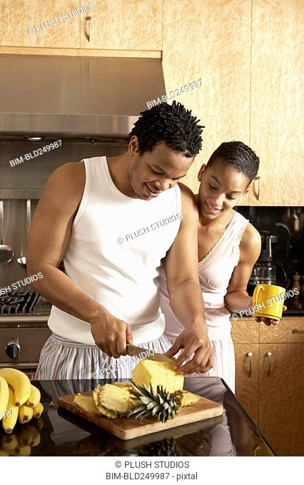 Couple wearing pajamas cutting pineapple in domestic kitchen