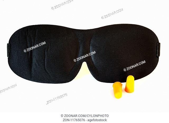 Black sleeping mask with orange ear plugs isolated on a white background. Studio shot