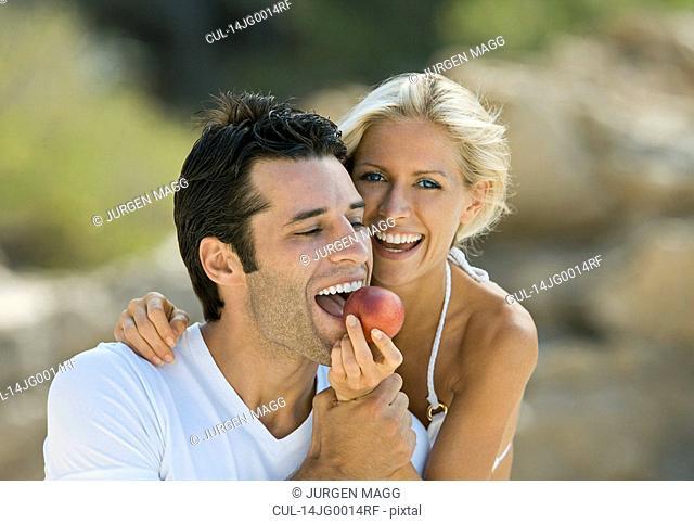A female feeding a latin man a nectarine