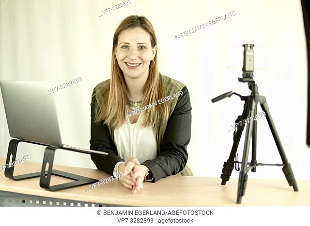 woman at lectern with laptop computer, recording online conference with phone, in Cottbus, Brandenburg, Germany