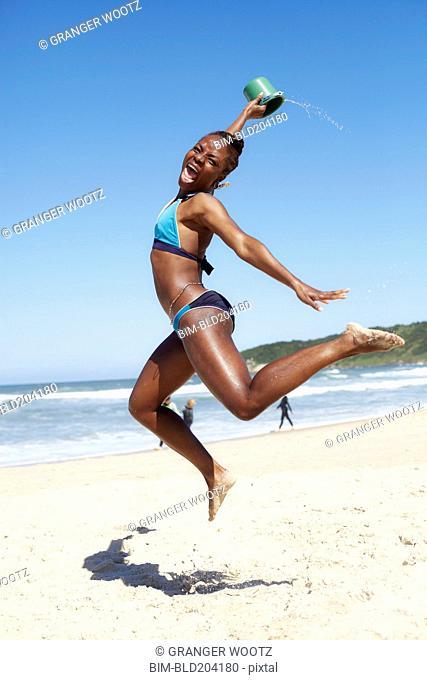Black woman jumping for joy on beach