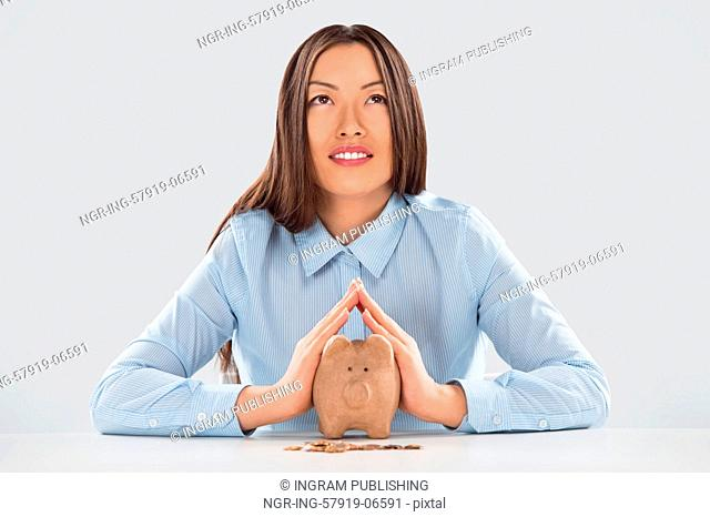 Happy business woman covering piggy bank with two hands - safety for your money concept
