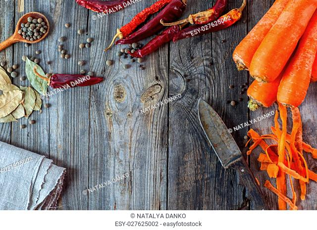 Carrot, chili and spices on gray wooden surface, top view, an empty space in the middle