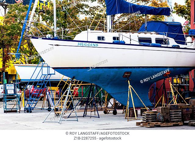 Two sailing vessels on supports for dry-land repairs and overhaul, Granville Island, Vancouver