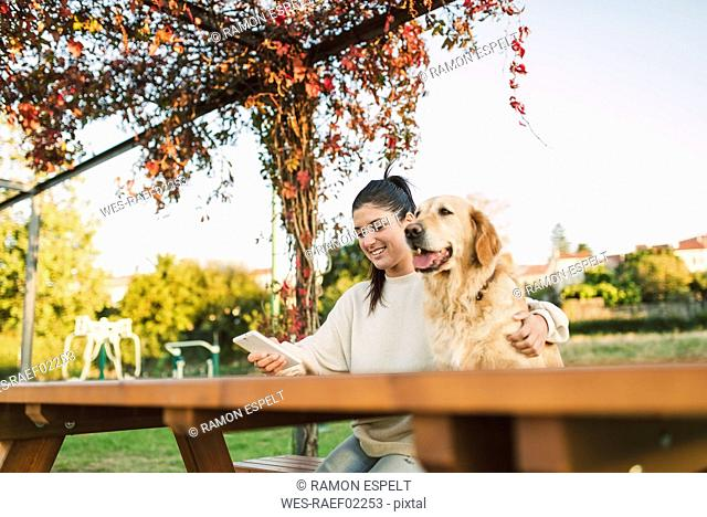 Smiling young woman with cell phone and her Golden retriever dog resting in a park