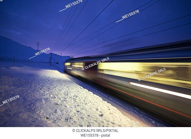 Bernina Express train runs fast in the snowy landscape at dusk Bernina Pass Canton of Graubünden Engadine Switzerland Europe
