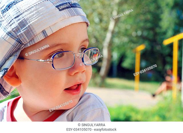 Little cute boy in glasses and cap looks away and smiles at summer day