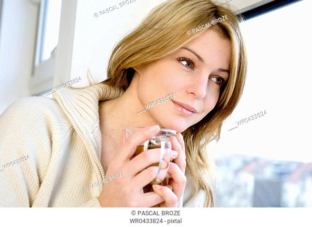 Close-up of a young woman holding a cup of herbal tea