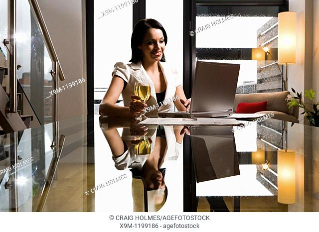 Woman using her laptop at home with a glass of wine