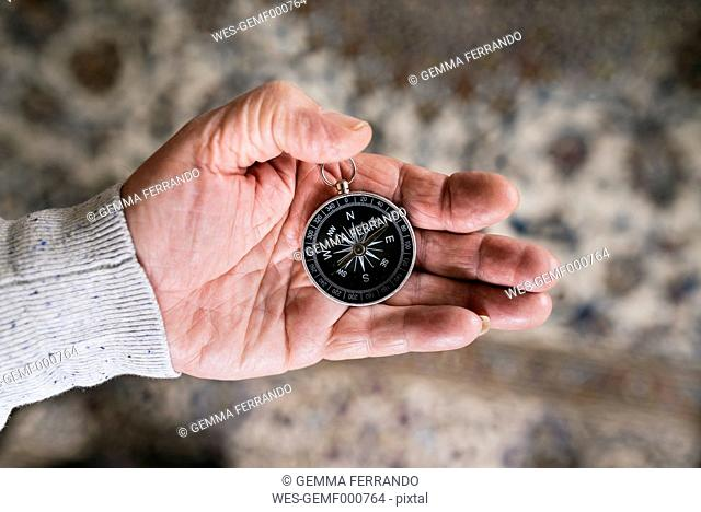 Hand of senior man holding compass, close-up