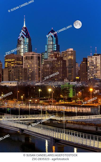 Philly Skyline Full Moon - A view to the Philadelphia Skyline during the blue hour at twilight. The illuminated urban skyline shows One and Two Liberty Place...
