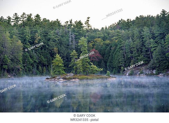 Mist rising on Bunnyrabbit Lake at dawn on La Cloche Silhouette Trail, Killarney Provincial Park, Ontario, Canada, North America