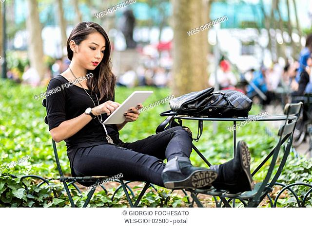 USA, New York, young woman sitting at city park using tablet