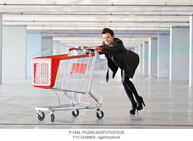 Young woman pushing empty shopping cart