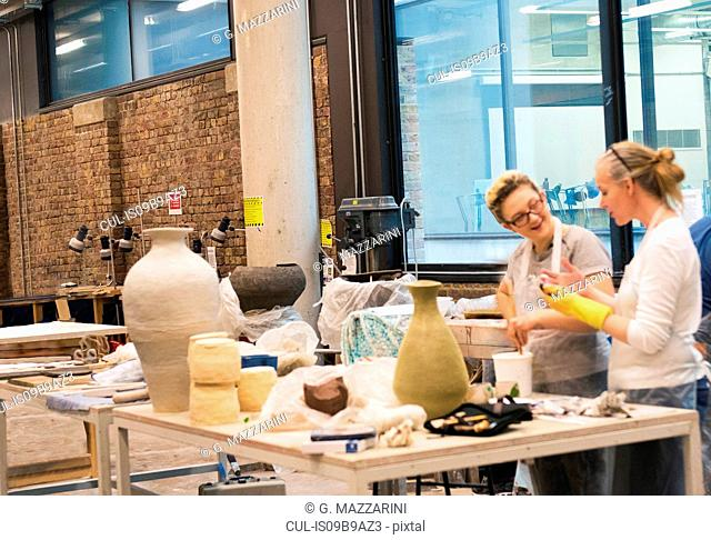 Colleagues in art studio making pottery