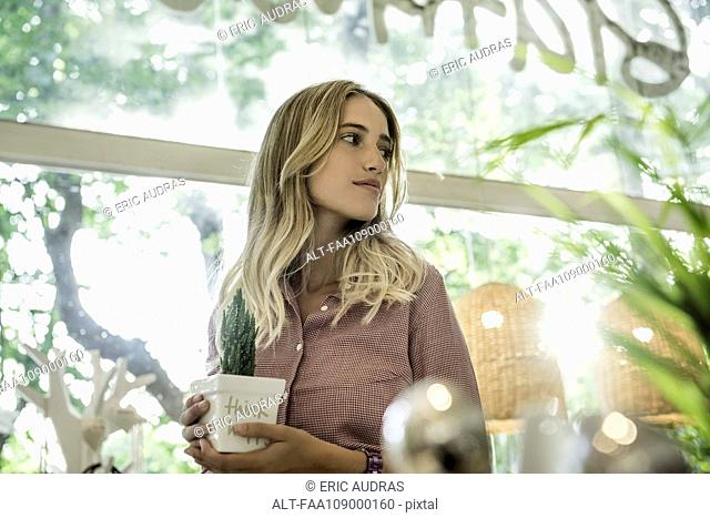 Young woman holding potted plant in shop, looking away in thought