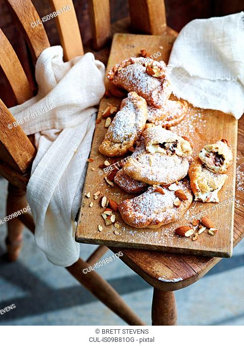 Cannoli calzone dusted with sugar, on serving board