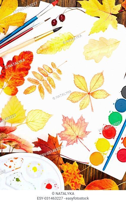 Watercolor painting with autumn leaves, paint, brushes, palette and colorful autumn leaves on wooden background. Top view