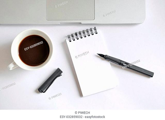 Coffee cup, spiral notebook, computer keyboard, and pen on white background - taken in natural light with strong shadow to create realistic indoor mood