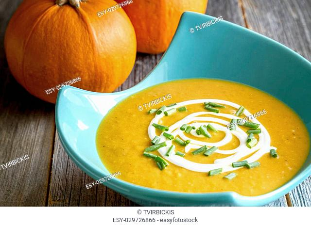 Pumpkin squash soup with cream and chives in bright blue modern bowl with two whole orange pumpkins