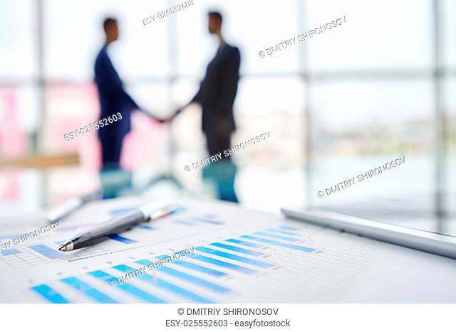 Pen and document with chart on background of office workers
