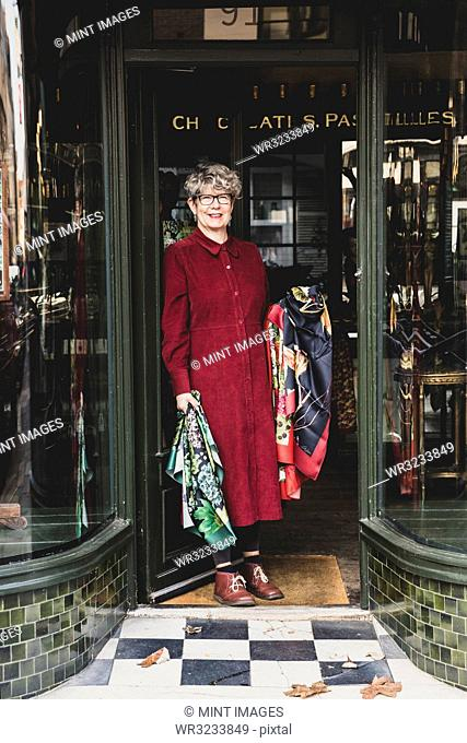 Smiling senior woman wearing glasses and red dress standing front of interior design store, looking at camera