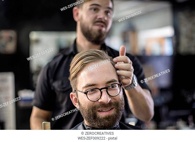 Barber and customer, smiling
