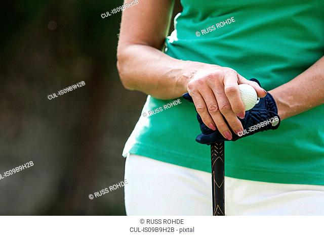 Cropped view of woman wearing golf glove holding golf ball and club
