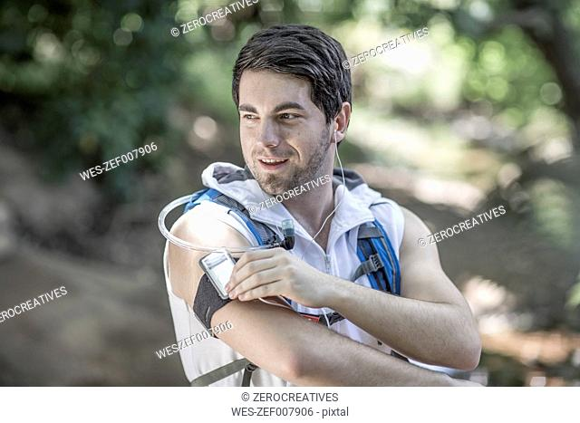 Man running in forest listening to music