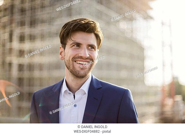 Portrait of smiling businessman in front of construction site looking sideways