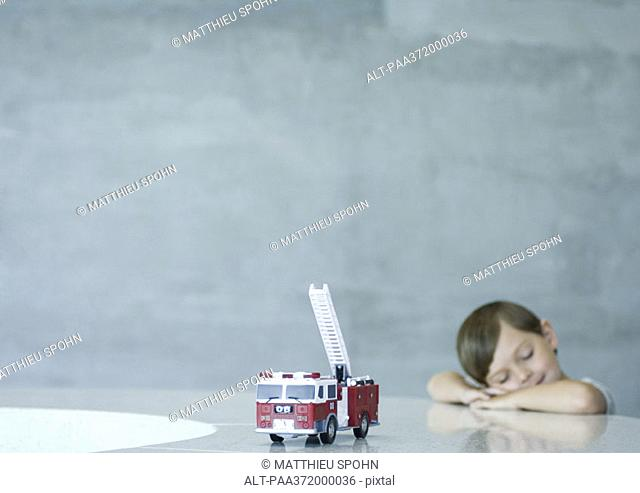 Boy with eyes closed, toy fire engine in foreground