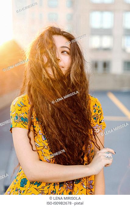 Portrait of young girl pulling long wavy hair across face in parking lot