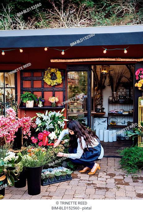 Mixed race florist arranging flowers outside shop