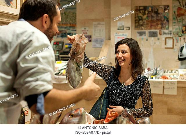 Woman buying fresh fish fishmonger