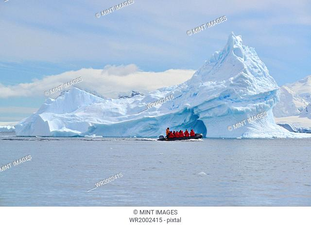 View of a group of people in a rubber boat near a towering iceberg in the Antarctic
