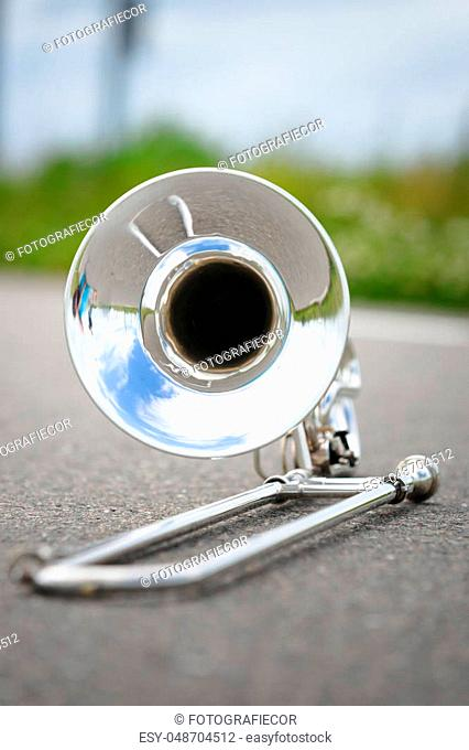 Close up of single silver trombone in an outdoor situation