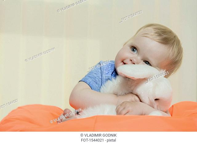 Close-up of cute smiling girl holding stuffed toy while sitting on bean bag at home