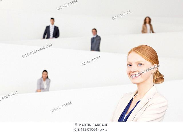 Portrait of smiling businesswoman with co-workers on staircase in background