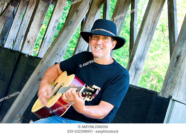 A man in jeans and cowboy hat plays guitar at the covered bridge
