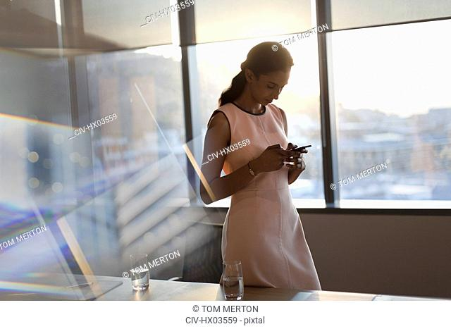 Businesswoman texting with cell phone in sunny conference room