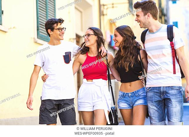Group of friends walking and laughing together in the city