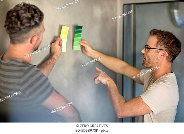Two men holding colour swatches against bare wall