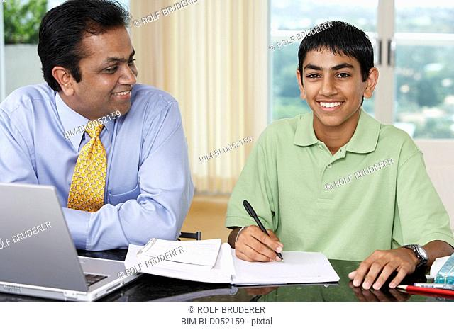 Middle Eastern father helping son with homework